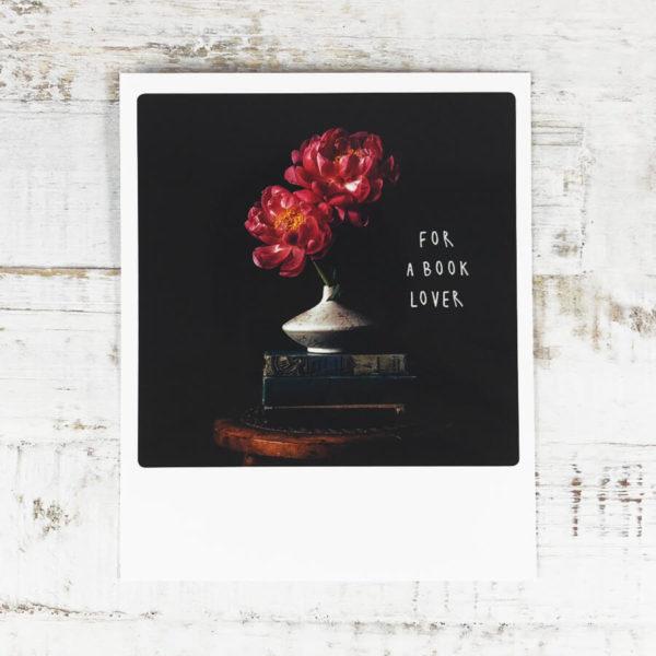 """Polaroid Karte mit Aufschrift """"For a book lover"""" und einer Blumenvase, die auf einem Stapel Büchern steht."""
