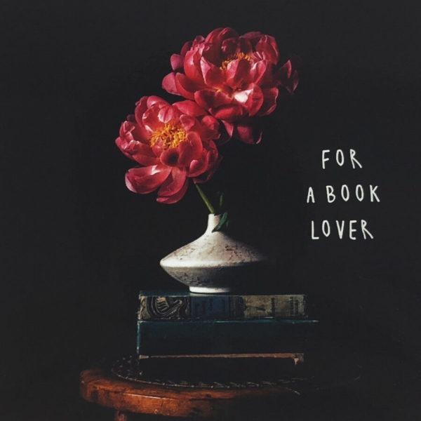 """Nahaufnahme der Polaroid Karte mit Aufschrift """"For a book lover"""" und einer Blumenvase, die auf einem Stapel Büchern steht."""