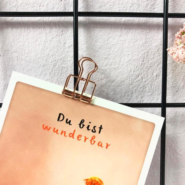 """Nahaufnahme des schwarzen Fotogitters mit LED Beleuchtung, an das eine Postkarte mit der Aufschrift """"Du bist wunderbar"""" mit einem rosé goldenen Paper Clips angebracht ist."""