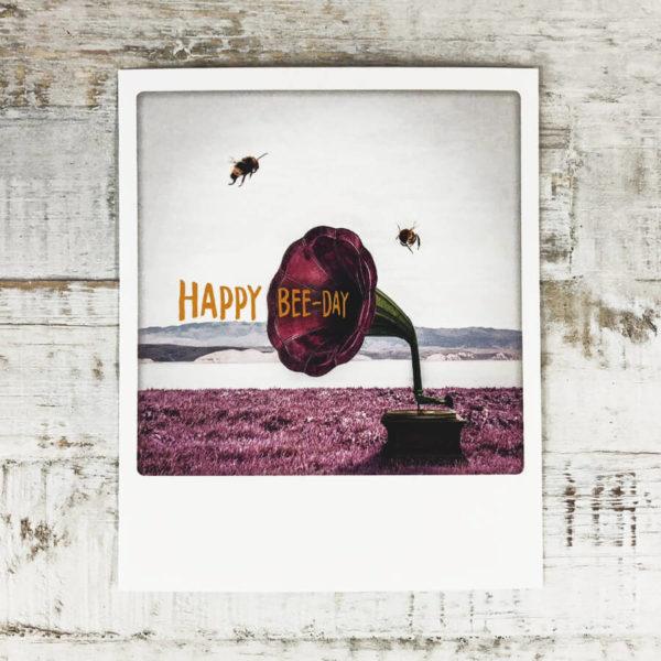"""Polaroid Karte mit Aufschrift """"Happy Bee-Day"""" und zwei Bienen, die um ein Megaphone fliegen."""