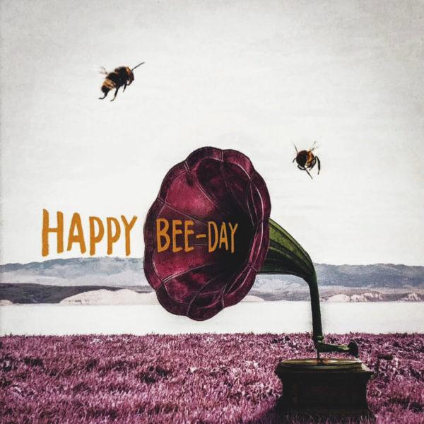 """Nahaufnahme der Polaroid Karte mit Aufschrift """"Happy Bee-Day"""" und zwei Bienen, die um ein Megaphone fliegen."""