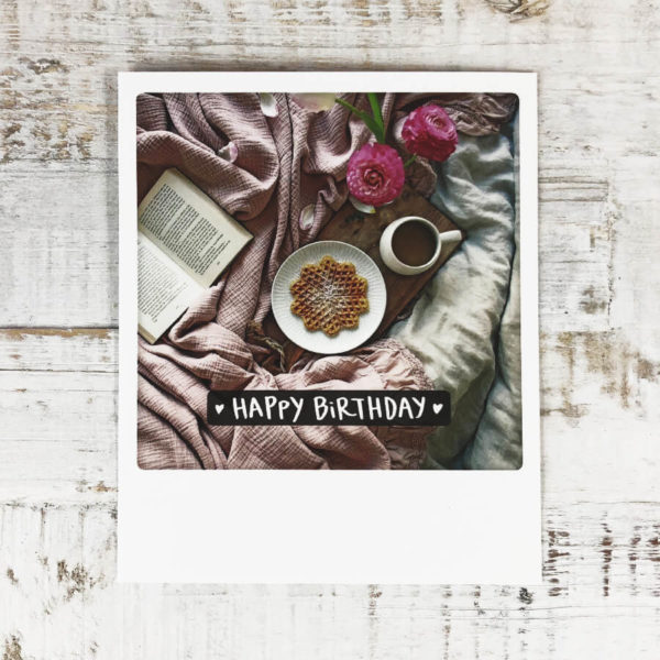 """Polaroid Karte mit Aufschrift """"Happy Birthday"""" und gemütlichem Bett mit Buch, Blumen und Frühstückstablett."""