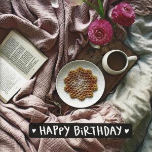 """Nahaufnahme der Polaroid Karte mit Aufschrift """"Happy Birthday"""" und gemütlichem Bett mit Buch, Blumen und Frühstückstablett."""