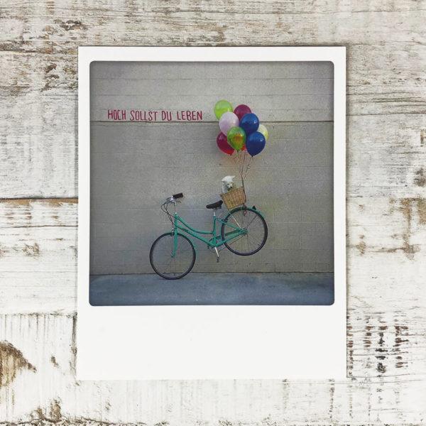 """Polaroid Karte mit Aufschrift """"Hoch sollst du leben"""" und Fahrrad mit Hund im Korb, das von Luftballons in die Luft gehoben wird."""