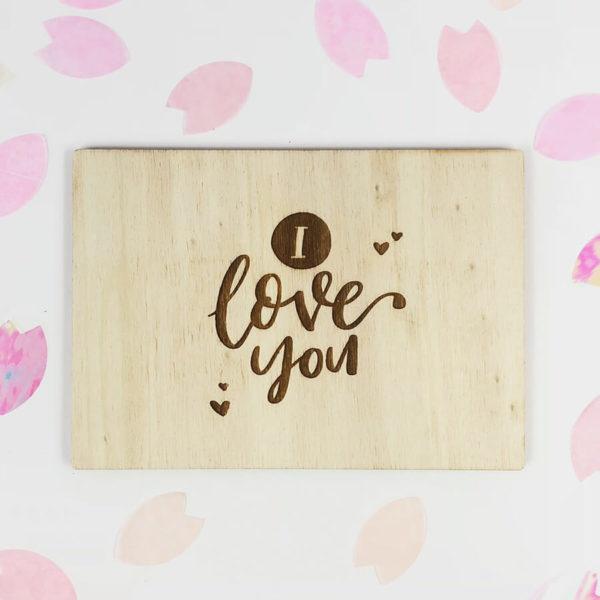 """Holzpostkarte mit Aufschrift """"I love you"""". Von oben fotografiert."""