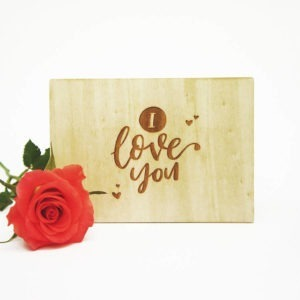 """Holzpostkarte mit Aufschrift """"I love you"""". Neben einer roten Rose vor weißem Hintergrund."""
