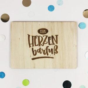 """Holzpostkarte mit Aufschrift """"Im Herzen barfuß"""". Von oben fotografiert."""
