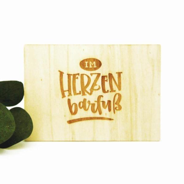 """Holzpostkarte mit Aufschrift """"Im Herzen barfuß"""". Neben grünen Blättern vor weißem Hintergrund."""
