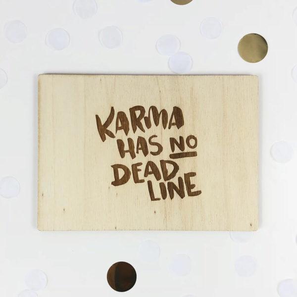 """Holzpostkarte mit Aufschrift """"Karma has no Deadline"""". Von oben fotografiert."""