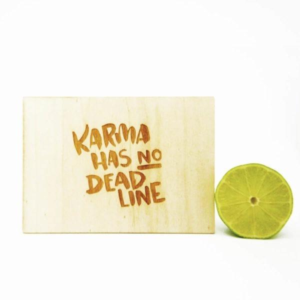 """Holzpostkarte mit Aufschrift """"Karma has no Deadline"""". Neben einer aufgeschnittenen Limette vor weißem Hintergrund."""