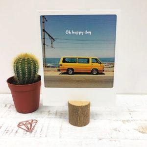 Kartenhalter aus Holz mit Postkarte, neben einem Kaktus und einer rosé goldenen Papierklammer.
