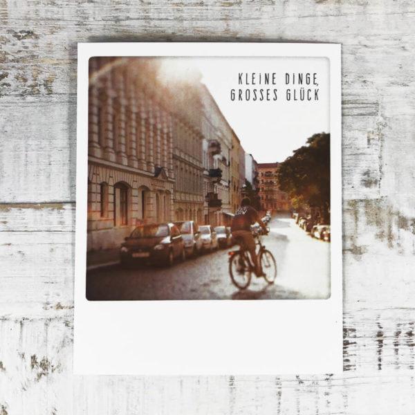 """Polaroid Karte mit Aufschrift """"Kleine Dinge, großes Glück"""" und Mann auf einem Fahrrad, der auf einer Straße fährt an deren Rand viele Autos parken."""