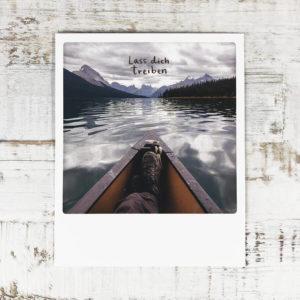 """Polaroid Karte mit Aufschrift """"Lass dich treiben"""" und Mann in einem Boot, der die Beine übereinander geschlagen hat."""