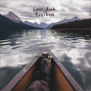"""Nahaufnahme der Polaroid Karte mit Aufschrift """"Lass dich treiben"""" und Mann in einem Boot, der die Beine übereinander geschlagen hat."""