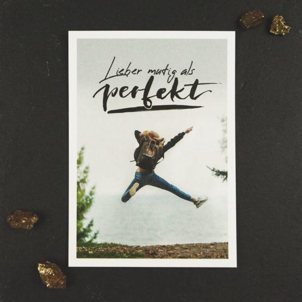"""Postkarte mit Aufschrift """"Lieber mutig als perfekt"""" und einer jungen Frau, die vor Freude in die Luft springt. Fotografiert vor einem schwarzen Hintergrund mit gold schimmernden Steinen."""