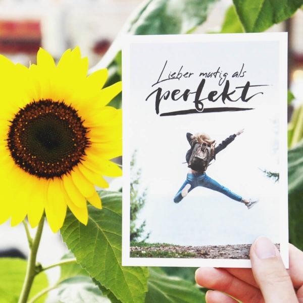 """Postkarte mit Aufschrift """"Lieber mutig als perfekt"""" und einer jungen Frau, die vor Freude in die Luft springt. Neben der Karte ist eine Sonnenblume. Designt von Mint & Limes."""
