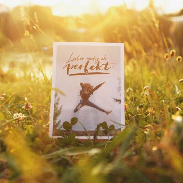 """Postkarte mit Aufschrift """"Lieber mutig als perfekt"""" und einer jungen Frau, die vor Freude in die Luft springt. Aufgenommen im Sonnenuntergang."""