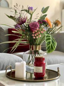 Blumen und Kerzen auf einem Tablett vor einem Sofa mit farbigen Kissen