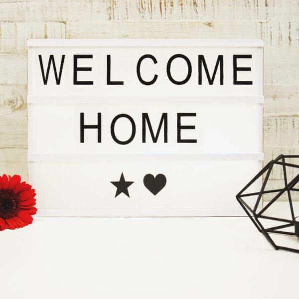 """Lightbox mit Holz Gehäuse und der Aufschrift """"Welcome Home"""" neben einer roten Blume und einem schwarze Teelicht vor hellem Hintergrund."""