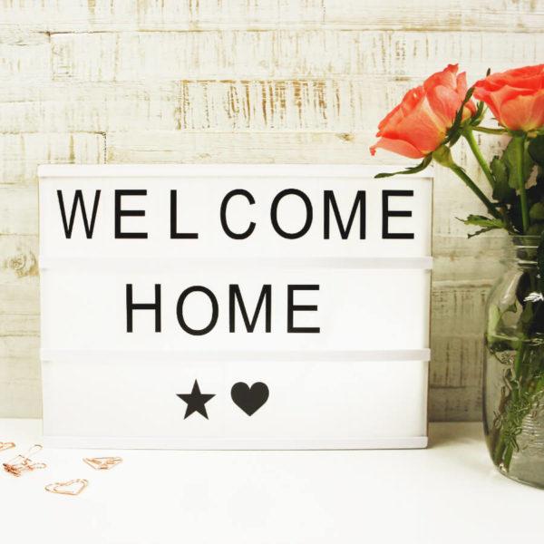 """Lightbox mit Holz Gehäuse und der Aufschrift """"Welcome Home"""" neben einer Blume und mehreren rosé goldenen Paper Clips vor hellem Hintergrund."""