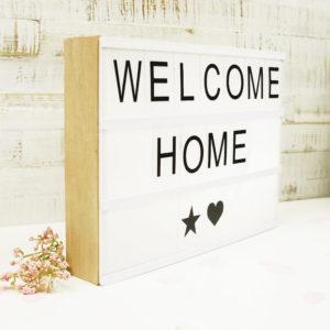 """Lightbox mit Holz Gehäuse und der Aufschrift """"Welcome Home"""" neben einer Blume vor weißem Hintergrund."""