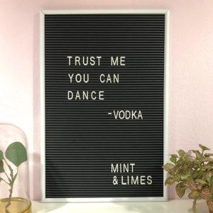 """Schwarzes Message Board mit weißen Buchstaben und der Aufschrift """"Trust me you can dance - Vodka"""" neben zwei Blumen als Dekoration."""