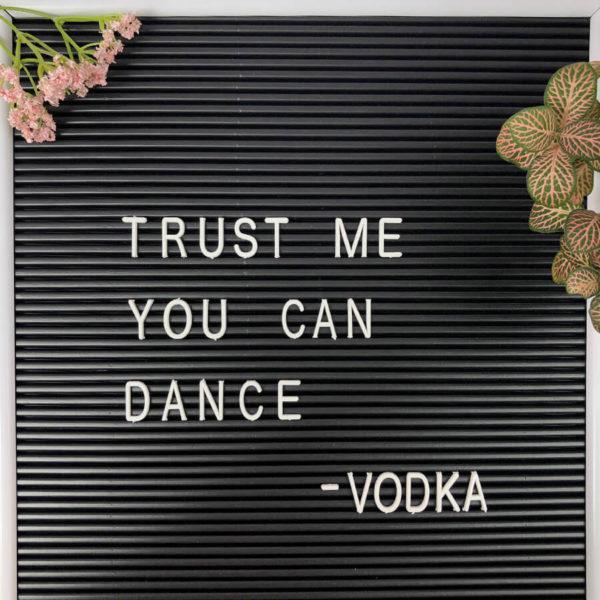 """Nahaufnahme eines schwarzen Message Boards mit weißen Buchstaben und der Aufschrift """"Trust me you can dance - Vodka"""" neben zwei Pflanzen als Dekoration."""