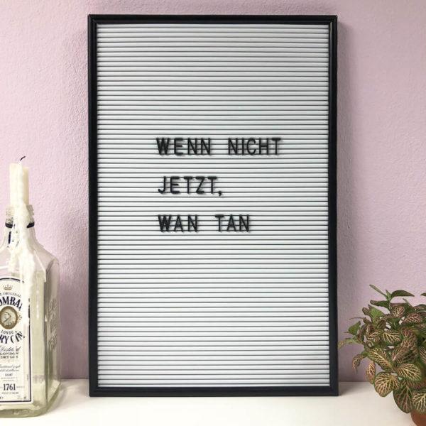 """Weißes Message Board mit schwarzen Buchstaben und der Aufschrift """"Wenn nicht jetzt, Wan Tan"""" neben einer Pflanze und einer Kerze."""