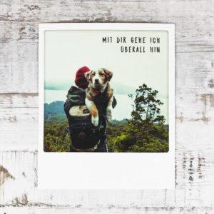 """Polaroid Karte mit Aufschrift """"Mit dir gehe ich überall hin"""" und Mann, der einen Hund im Arm hält."""