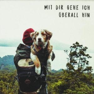 """Nahaufnahme der Polaroid Karte mit Aufschrift """"Mit dir gehe ich überall hin"""" und Mann, der einen Hund im Arm hält."""