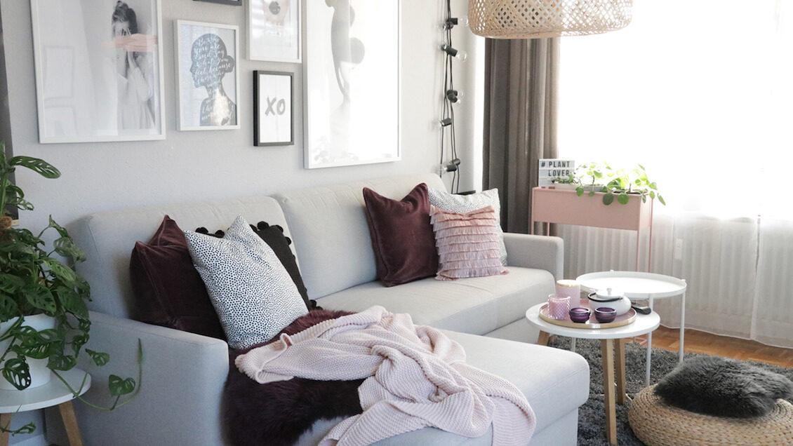 Gemütliches Wohnzimmer mit vielen Prints an der Wand, hellgrauem Sofa und wunderschöner Dekoration