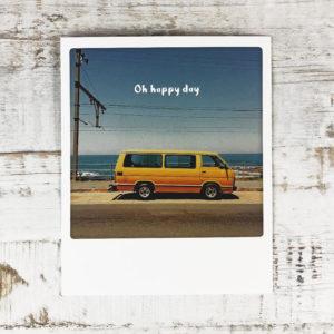 """Polaroid Karte mit Aufschrift """"Oh happy day"""" und gelbem Kleinbus, der am Meer parkt."""