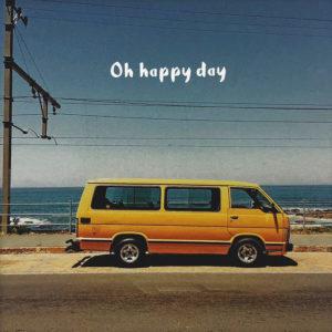 """Nahaufnahme der Polaroid Karte mit Aufschrift """"Oh happy day"""" und gelbem Kleinbus, der am Meer parkt."""