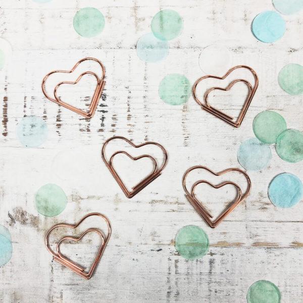Fünf rosé goldene Papierklammern in Herzform inmitten grünem Konfetti auf weißem Hintergrund.