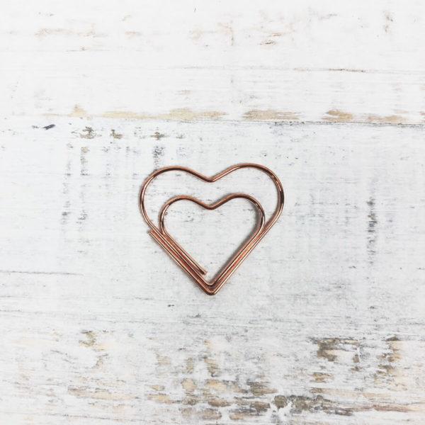 Eine rosé goldene Papierklammer in Herzform auf weißem Hintergrund.