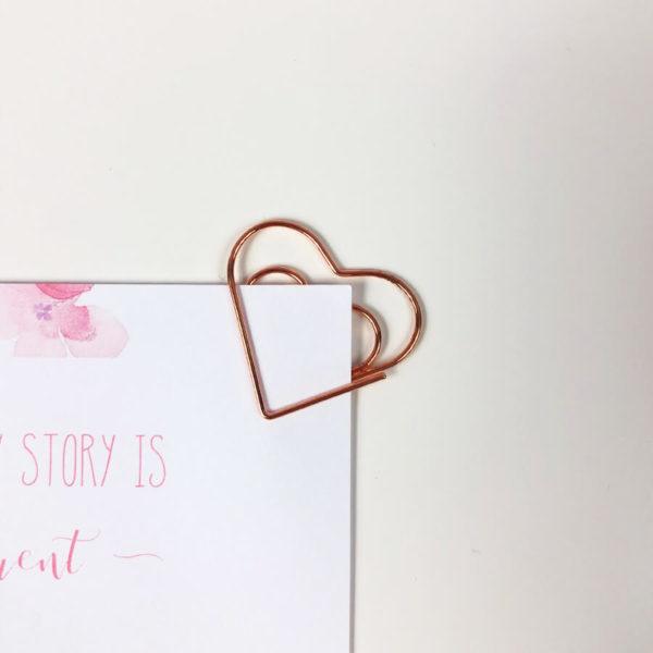 """Rosé goldener Paper Clip in Herzform an einem Notizzettel mit der Aufschrift """"Cause every story is different"""" vor weißem Hintergrund."""