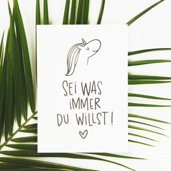 """Postkarte mit Aufschrift """"Sei was immer du willst!"""" mit Einhornkopf und Herz auf einem grünen Blatt."""