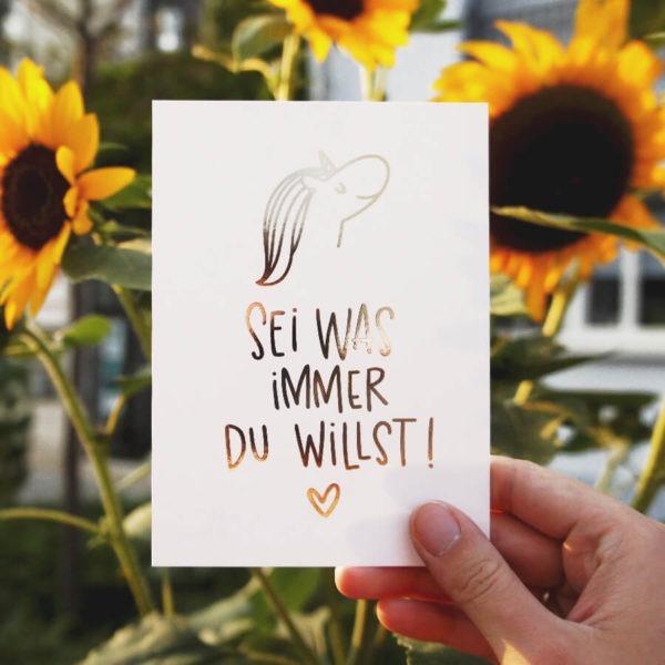 """Postkarte mit Aufschrift """"Sei was immer du willst!"""" mit Einhornkopf und Herz vor Sonnenblumen. Designt von Mint & Limes."""
