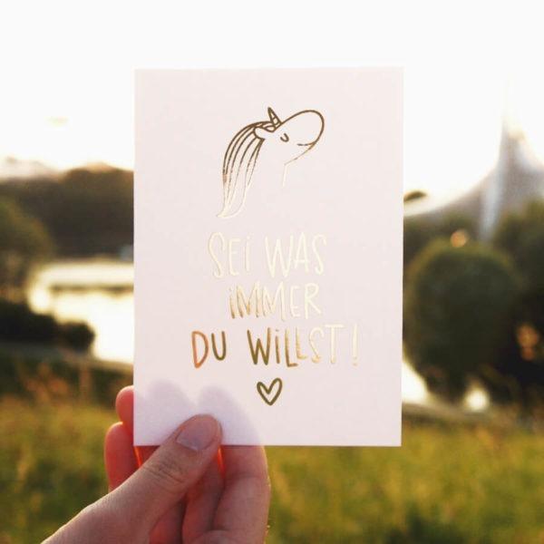 """Postkarte mit Aufschrift """"Sei was immer du willst!"""" mit Einhornkopf und Herz."""