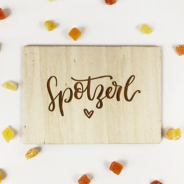 """Holzpostkarte mit Aufschrift """"Spotzerl"""" und kleinem Herz. Von oben fotografiert."""