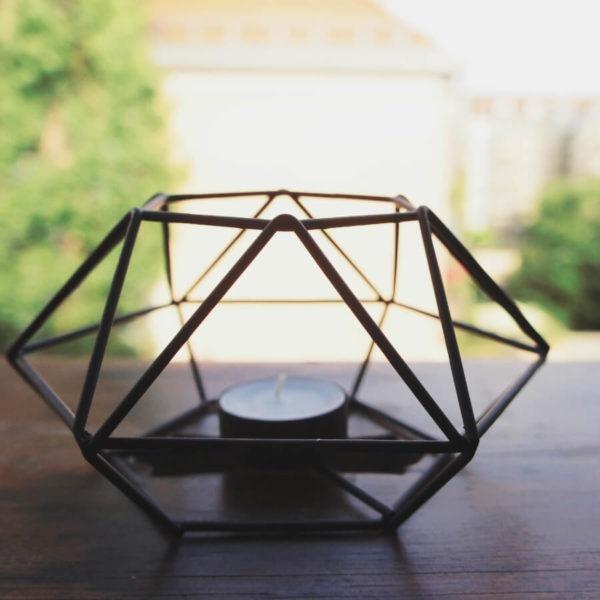Teelicht Prisma aus Metall, schwarz lackiert und einem Haus und Bäumen im Hintergrund.