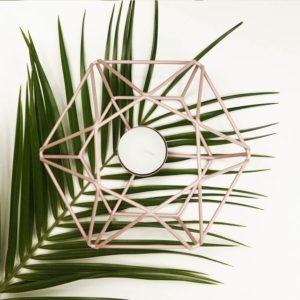 Teelicht Prisma aus Metall, rosa farbig lackiert. Teelicht von oben auf einem Palmwedel fotografiert.