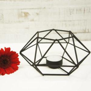 Teelicht Prisma aus Metall, schwarz lackiert. Bild von vorne neben einer roten Blume fotografiert.