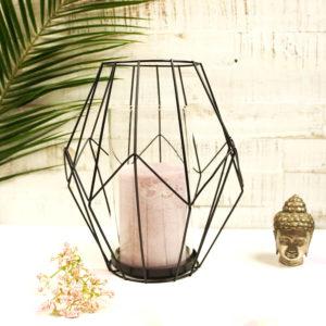 Schwarzes Teelicht aus Metall in moderner Prisma-Optik mit lilaner Kerze, dekoriert mit einem Blatt, einer Blume und einem Buddha Kopf.