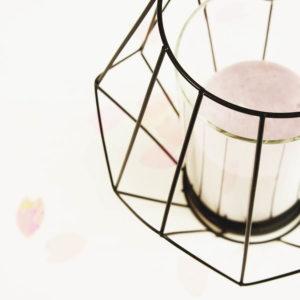 Schwarzes Teelicht aus Metall mit rosaner Kerze und Konfetti im Hintergrund.
