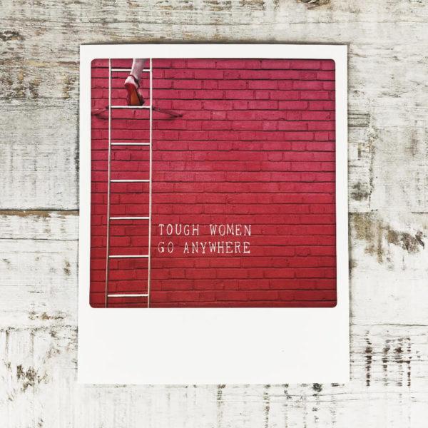 """Polaroid Karte mit Aufschrift """"Tough women go anywhere"""" und Frau in High Heels, die eine Leiter hochsteigt."""