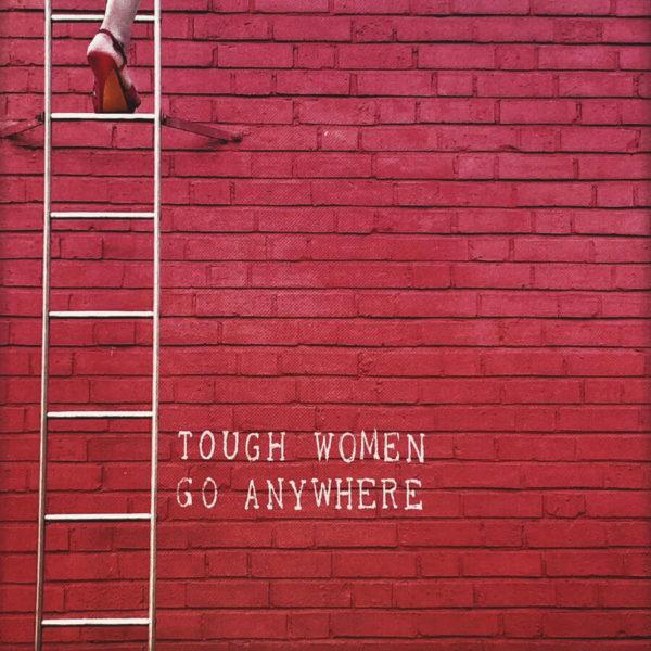 """Nahaufnahme der Polaroid Karte mit Aufschrift """"Tough women go anywhere"""" und Frau in High Heels, die eine Leiter hochsteigt."""
