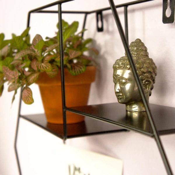 Wandregal Hexagon aus Metall mit schwarzem Lack. In Nahaufnahme mit Buddha Kopf und Pflanze.