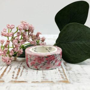 Washi Tape mit pinken Blumen vor Ästen auf einem Holzbrett liegend fotografiert.