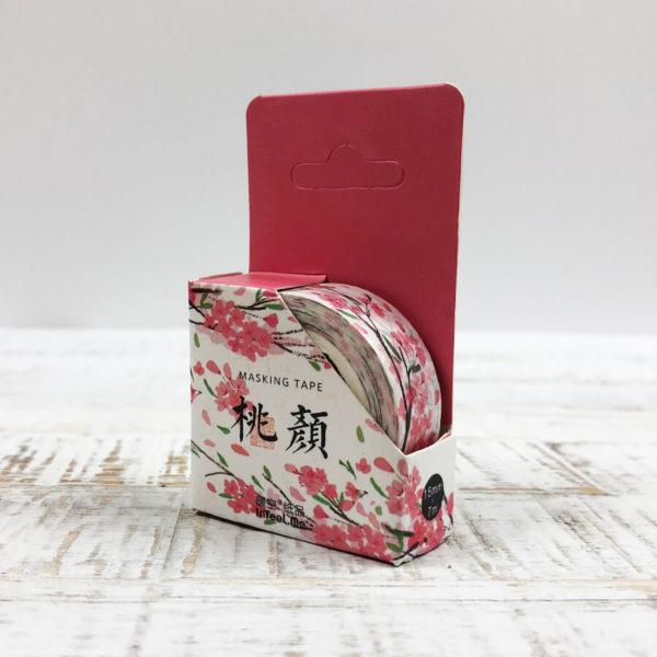 Washi Tape mit Blumenmuster in der Verpackung vor weißem Hintergrund.